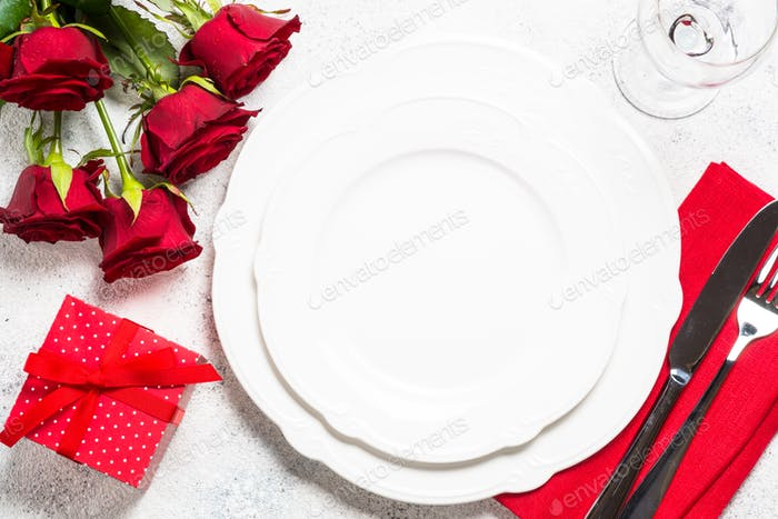 Holiday table setting with plate, cutlery and red roses.