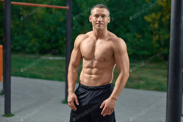 Muscular sportsman with naked torso posing outdoors