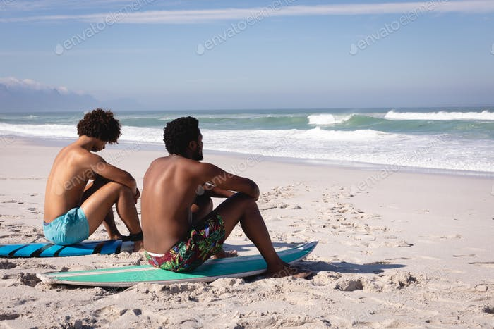 Young multi-ethnic men sitting on surfboards and looking at the sea on the beach in the sunshine