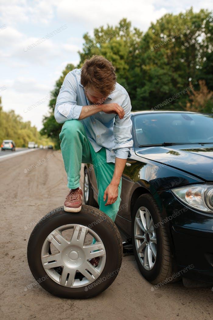 Autopannung, junger Mann stellt den Ersatzreifen