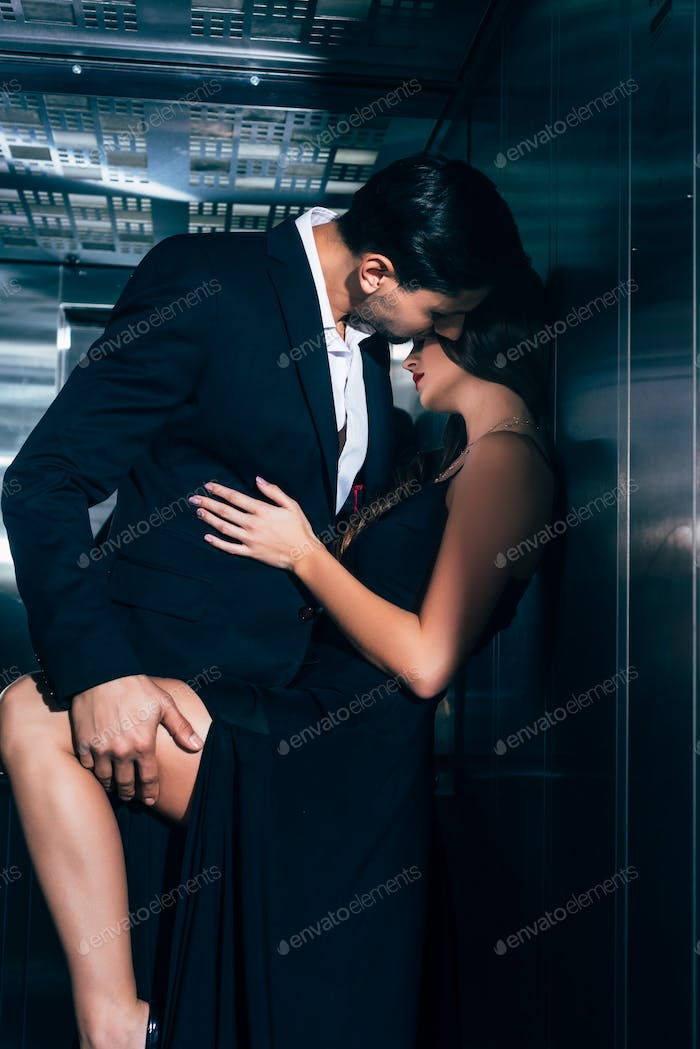 seductive couple kissing and hugging in elevator