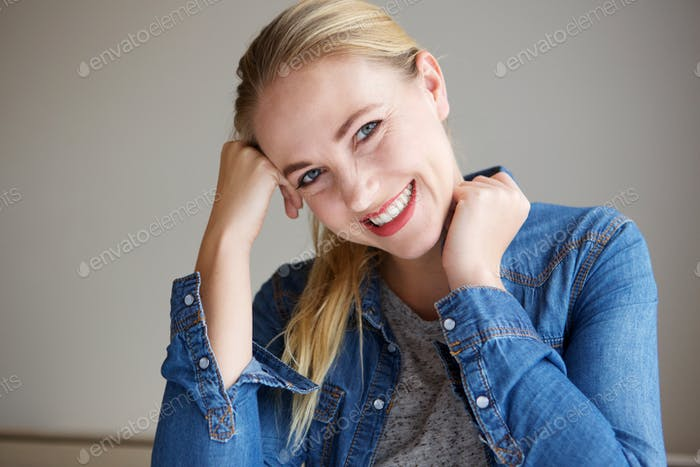 Close up young blond woman smiling and leaning on hand