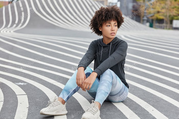 Outdoor shot of pensive dark skinned teenager dressed in casual sportsclothes, sneakers, sits on asp