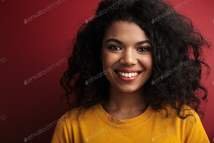 Image of beautiful brunette african american woman with curly hair smiling