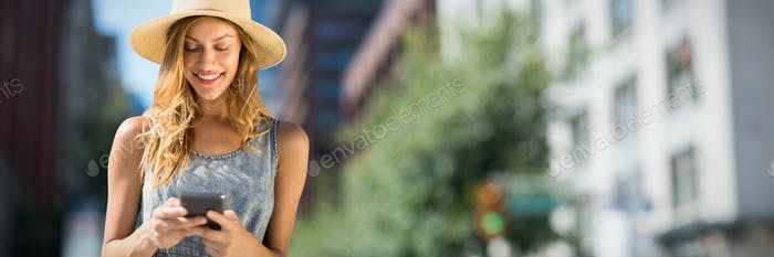 Composite image of beautiful woman using her mobile phone