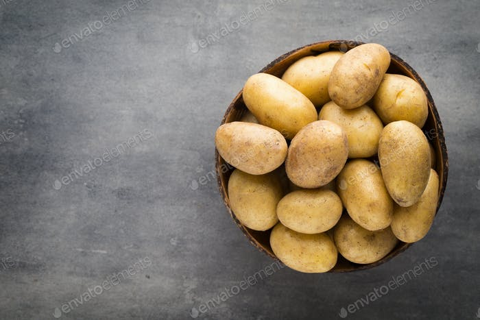 New potato on the bowl, gray background.