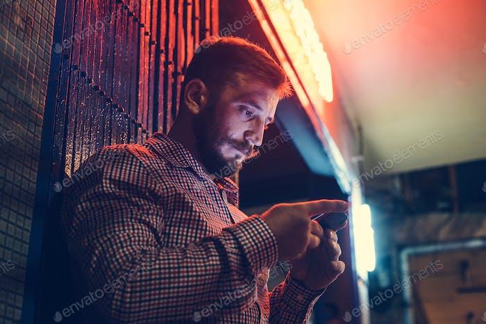 Nahaufnahme eines Mannes mit Mobiltelefon im Dunkeln mit langer Belichtung Licht