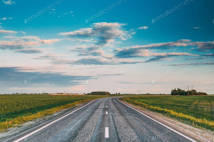 Asphalt Open Road Through Spring Fields And Meadows In Sunny Eve