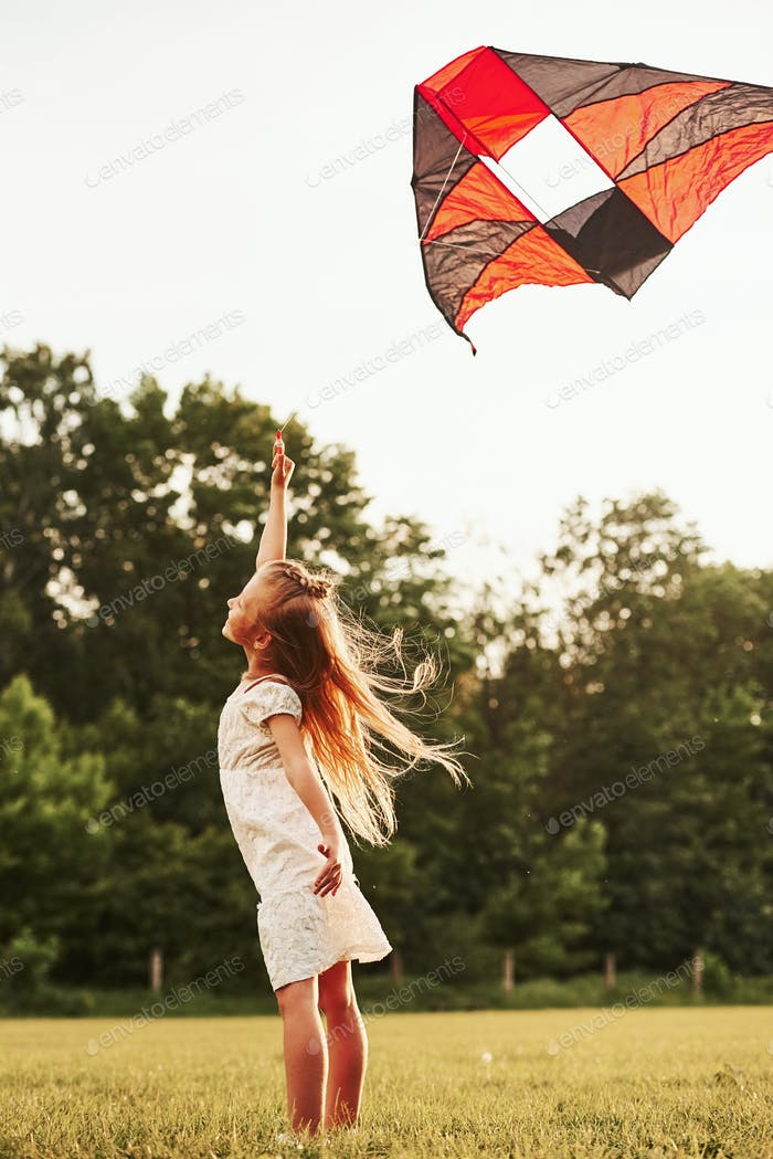 Feeling joy. Happy girl in white clothes have fun with kite in the field. Beautiful nature