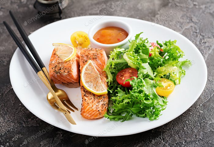 Baked salmon fillet with fresh vegetables salad. Healthy food. Ketogenic/paleo diet.