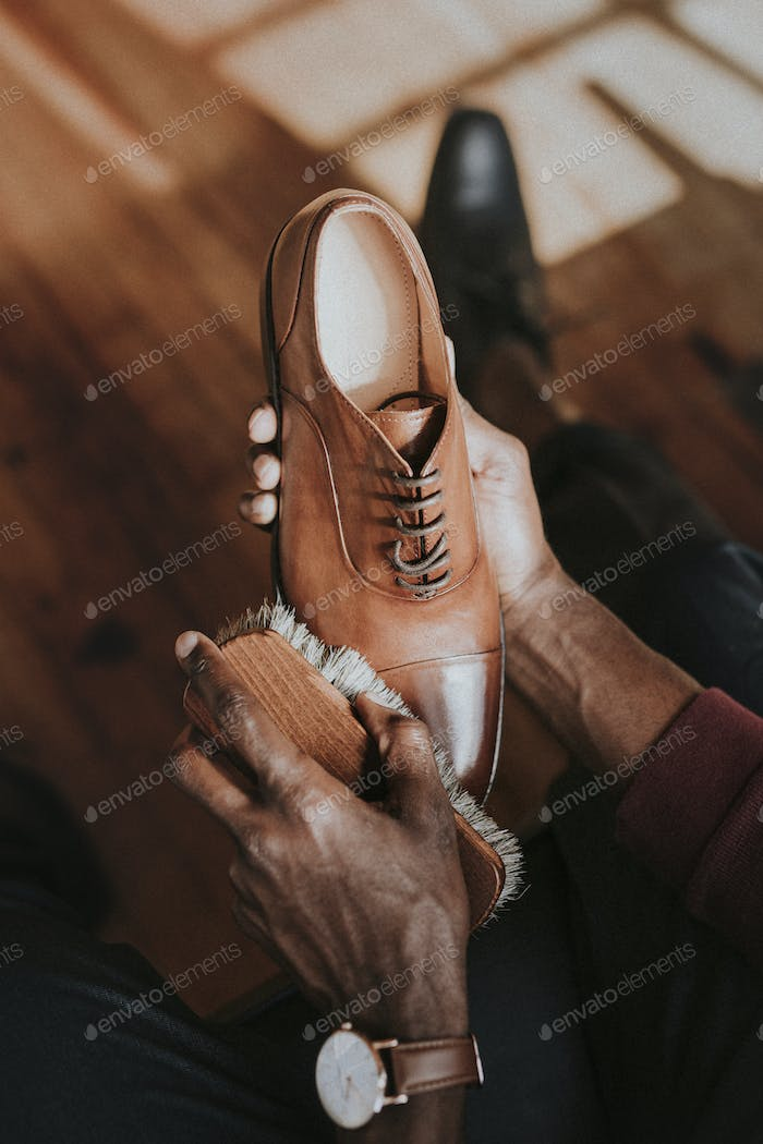 Man applying shoe polish to his brown leather shoes