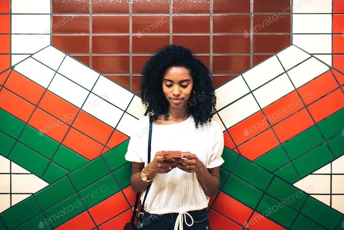 Frau mit Mobiltelefon im Stehen in U-Bahnstation