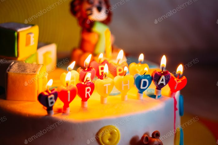 Happy Birthday Written In Lit Candles On Colorful Cake