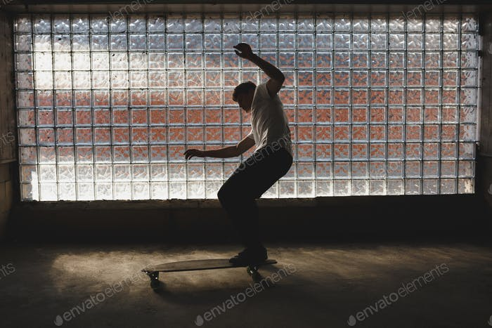 Photo of cool boy that skateboarding and making tricks with glass wall on background
