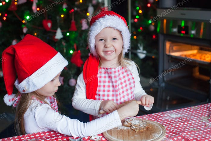 Little girls baking gingerbread cookies for Christmas in Santa hat