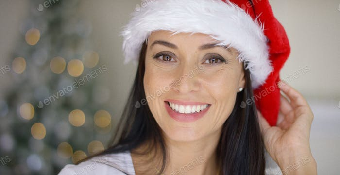 Lovely young woman in a red Santa hat