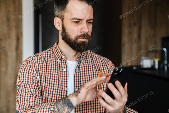 Serious brunette bearded man looking at mobile phone