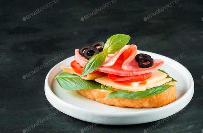 Fresh sandwich with ham, cheese, basil
