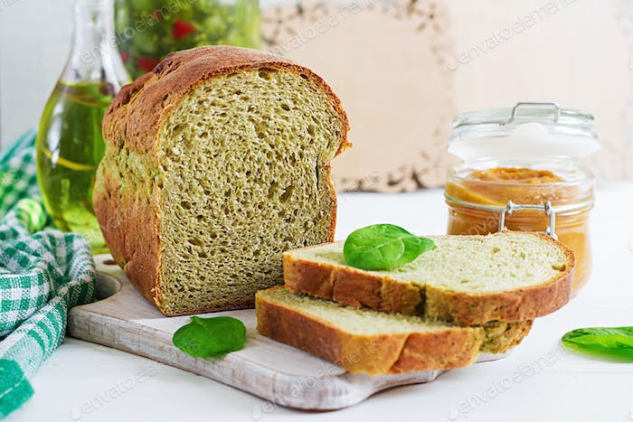 Freshly baked  spinach bread on a white wooden table. Rustic style. Bakery food.