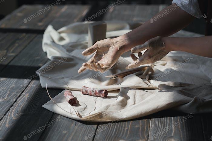 Hände in Ton gebeizt gehen geschnitten Werkzeug aus Holztisch zu nehmen, Kunsttherapie Konzept