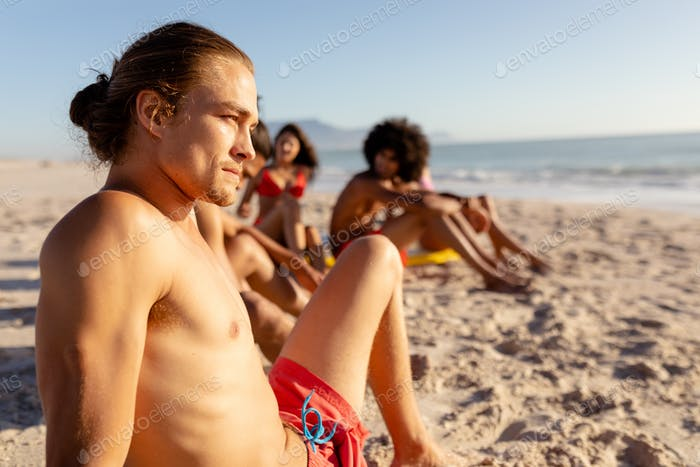 Mixed race friends laying on beach