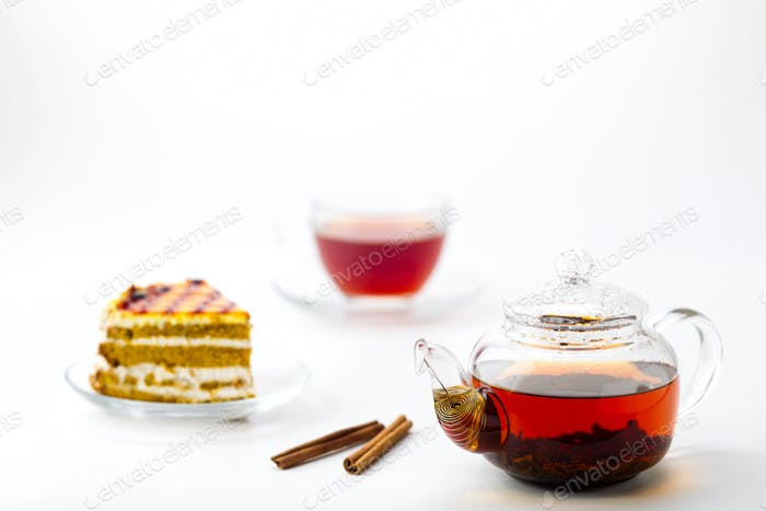 Teapot, tea cup and cake on white background
