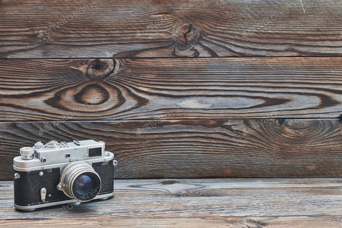 Vintage old retro rangefinder camera on wooden background