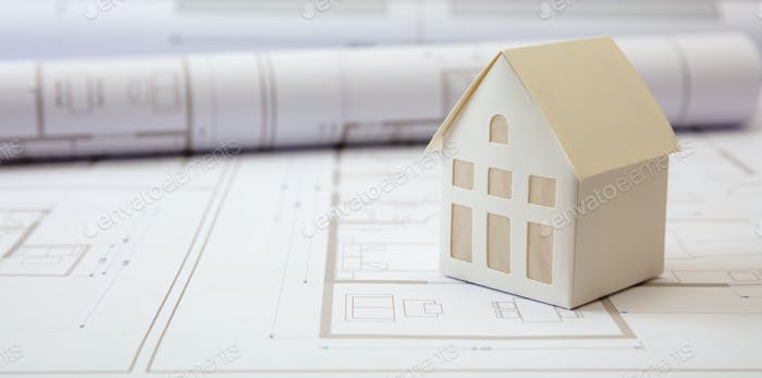 Construction concept. Residential building drawings and architectural house model on an office desk