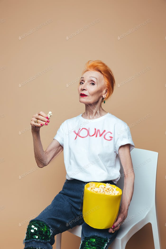 Mature redhead fashion woman sitting isolated