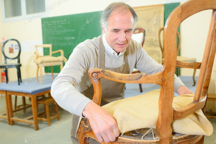 older man restoring a chair in his workshop