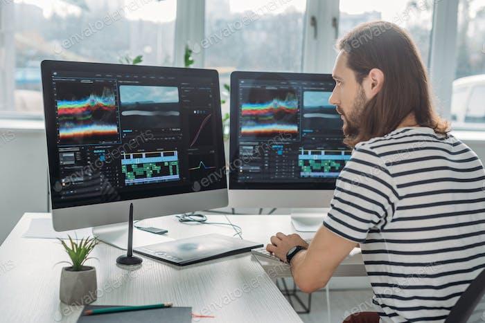 editor guapo sentado y trabajando cerca de los monitores de computadora