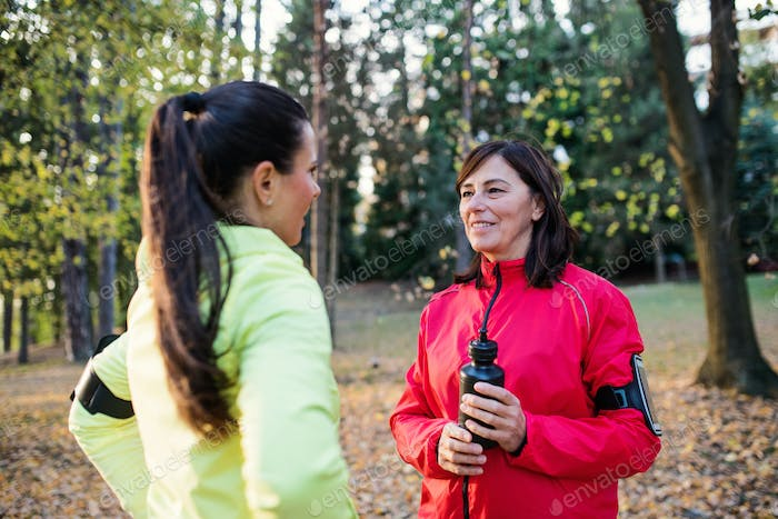 Female runners with water bottle and smartphones standing outdoors in forest.