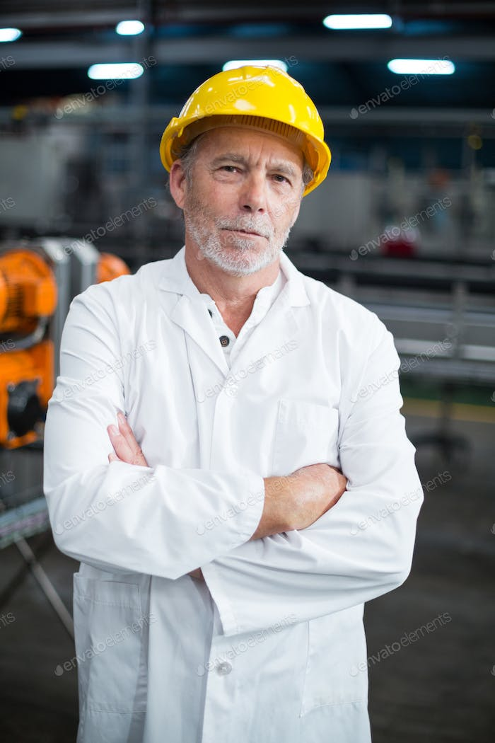 Portrait of factory engineer standing with his arms crossed