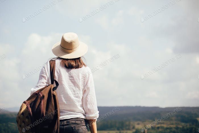 Stylish hipster girl with backpack traveling in sunny mountains