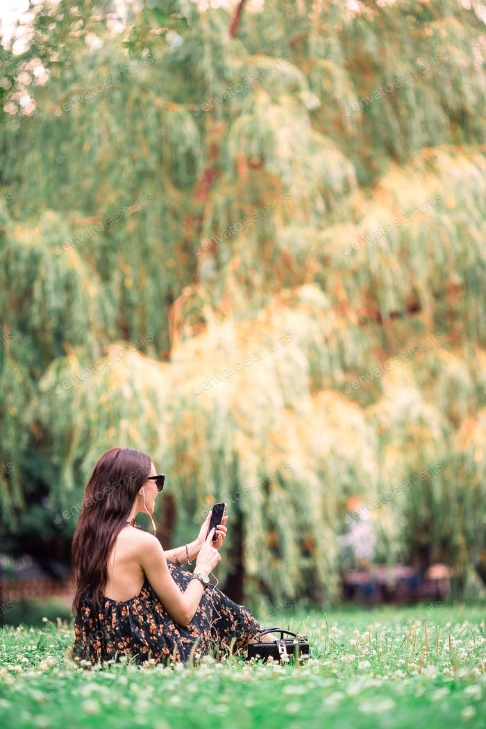 Cute woman is reading text message on mobile phone while sitting in the park