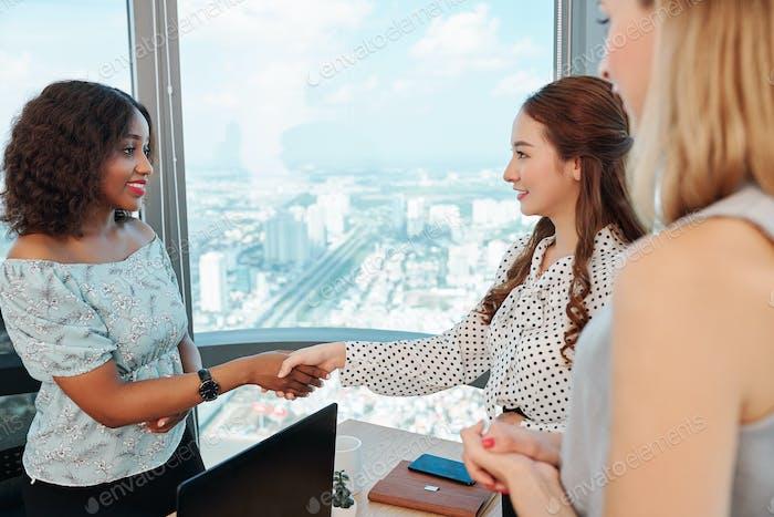 Female entrepreneur greeting business partner