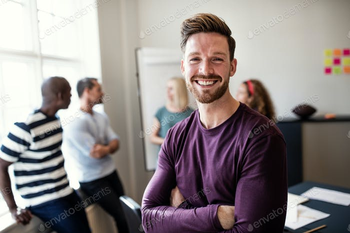 Smiling young designer standing in an office after a presentation