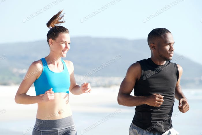 Fit young man and woman running at beach