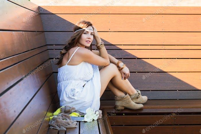 Junge Frau im Boho-Stil sitzen auf Holzbank und Träume