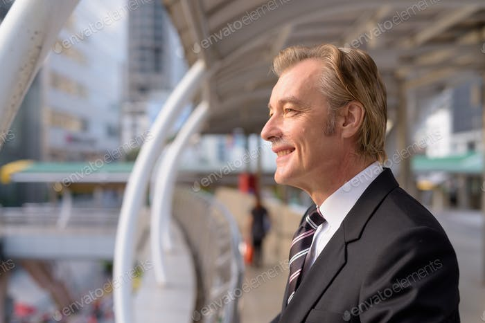 Profile view of happy mature handsome businessman looking at view of the city