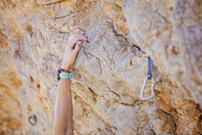 Closeup of climber's hand on cliff