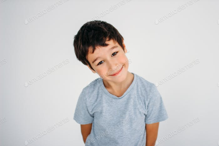 Cute smiling tween boy looking at camera on white background