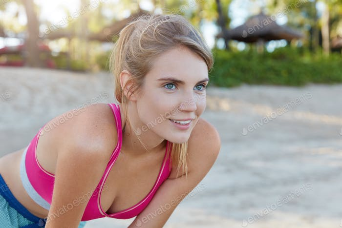 Photo of attractive sportswoman catches breath on beach after morning exercise, enjoys sunshine and