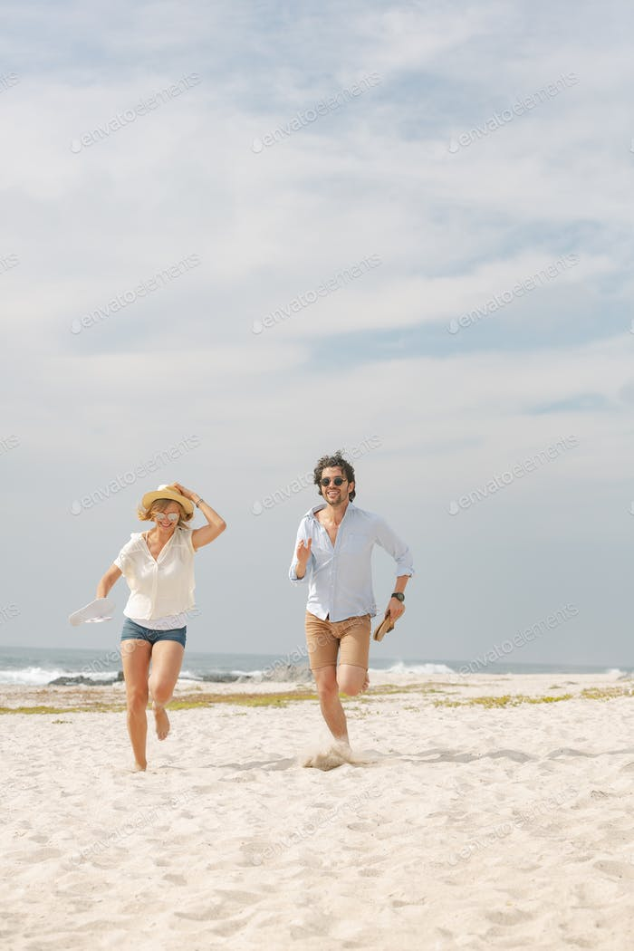 Front view of happy young Caucasian couple running at beach on sunny day. They are smiling