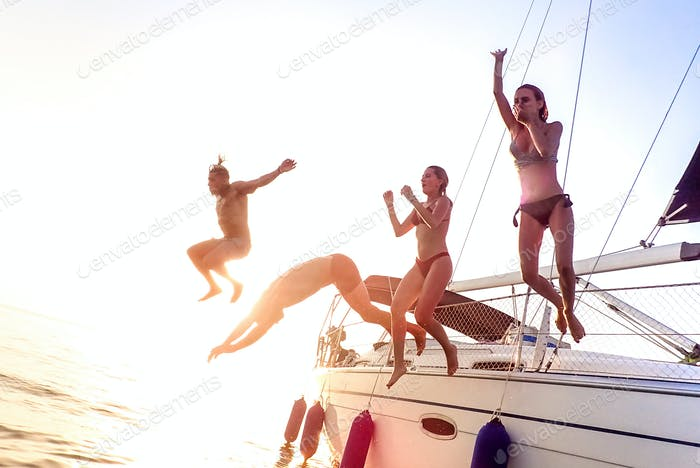 Young millenial friends jumping from sailboat at sea ocean trip