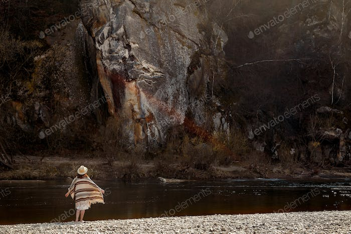 beautiful woman traveler  wearing hat and poncho, looking at amazing cliff