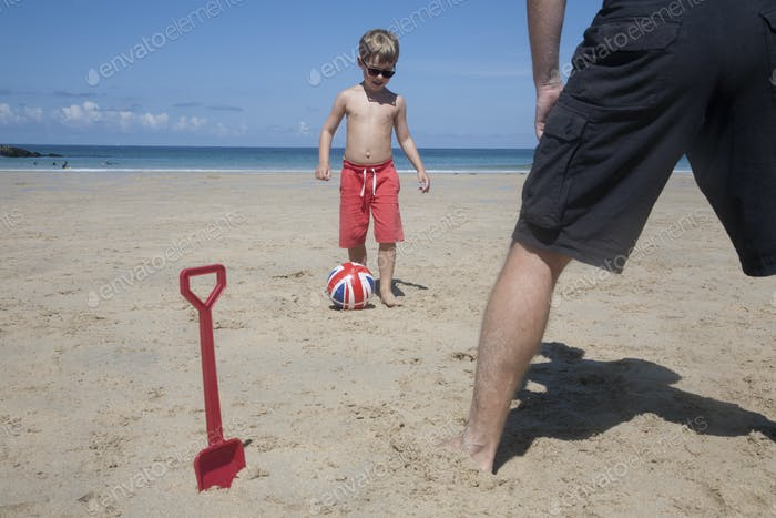 A boy playing football with a man on the sand. Father and son. A beach spade upright in the sand.
