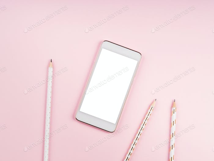 Mobile phone screen on pink background. Pencils