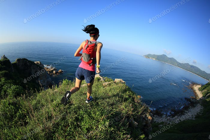 young fitness woman running on seaside mountain trail