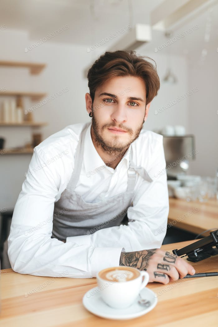 Young barista in apron and white shirt dreamily looking in camera on his workplace in coffee shop